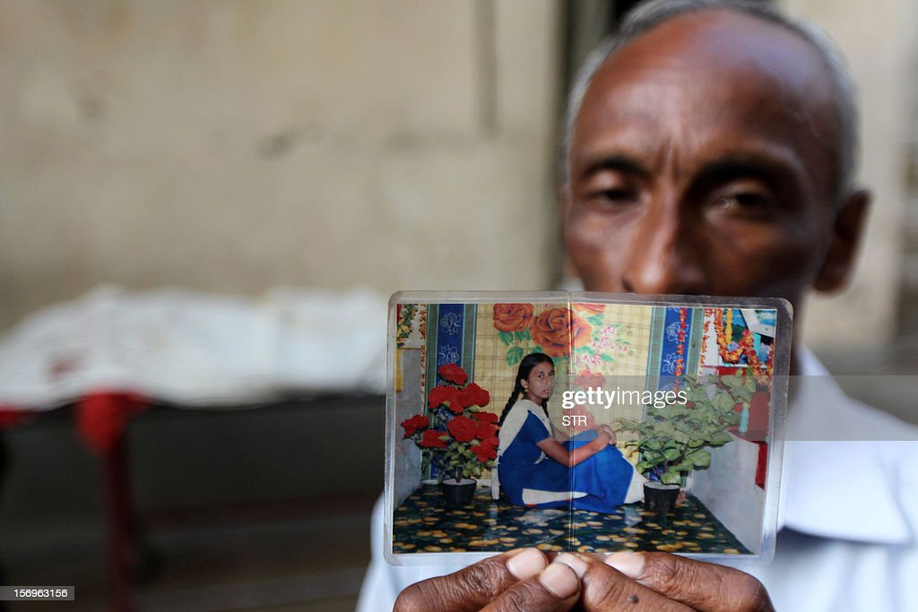 Bangladeshi Mohammad Ali holds up a photograph of his missing daughter who worked at a garment factory that burned down the day before, at the Dhaka Medical College Hospital, in Dhaka on November 26, 2012. Garment workers staged mass protests to demand the end to 'deathtrap' labour conditions after Bangladesh's worst-ever textile factory fire, as a new blaze sparked fresh panic and terror. Ahead of the first of a series of mass funerals for the 110 victims, survivors of Saturday night's blaze joined several thousand colleagues to block a highway and march in the manufacturing hub of Ashulia.