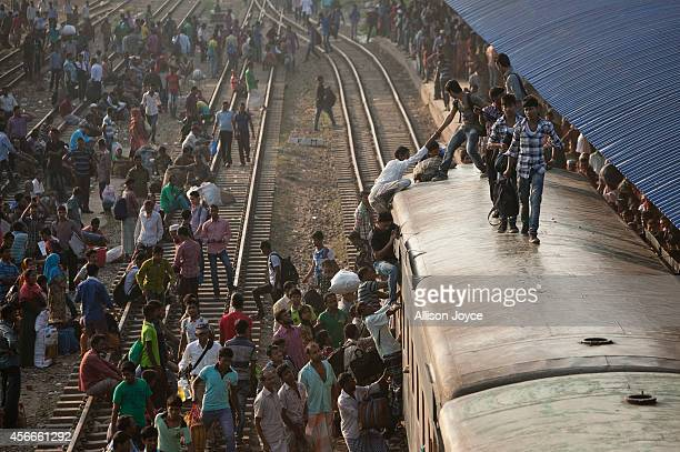 Bangladeshi Muslims climb on the roof of an overcrowded train as they head to their homes the day before the EidalAdha Festival October 5 2014 in...