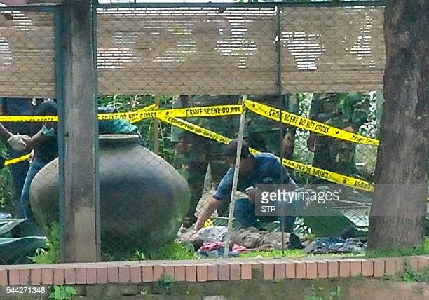 A Bangladeshi official examines a body believed to be of one of the attackers at an upscale cafe in Dhaka on July 2 after a bloody siege at the...