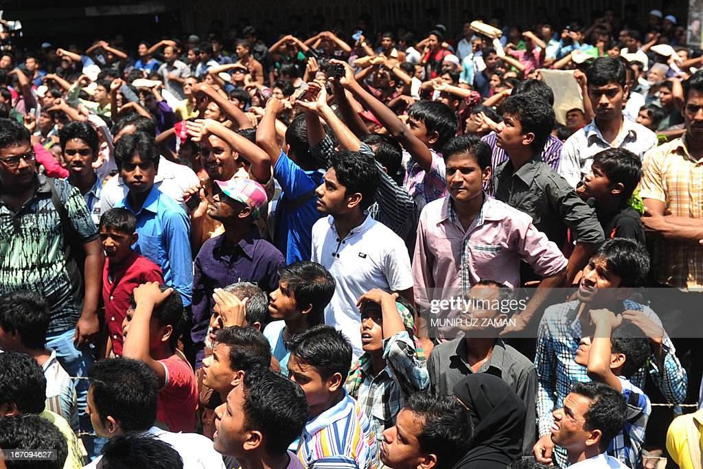Bangladeshi onlookers gather around as firefighters attempt to extinguish a blaze at a shopping centre in Dhaka on April 20, 2013. At least 12 fire fighting units rushed to the spot to control the blaze. AFP PHOTO/ Munir uz ZAMAN