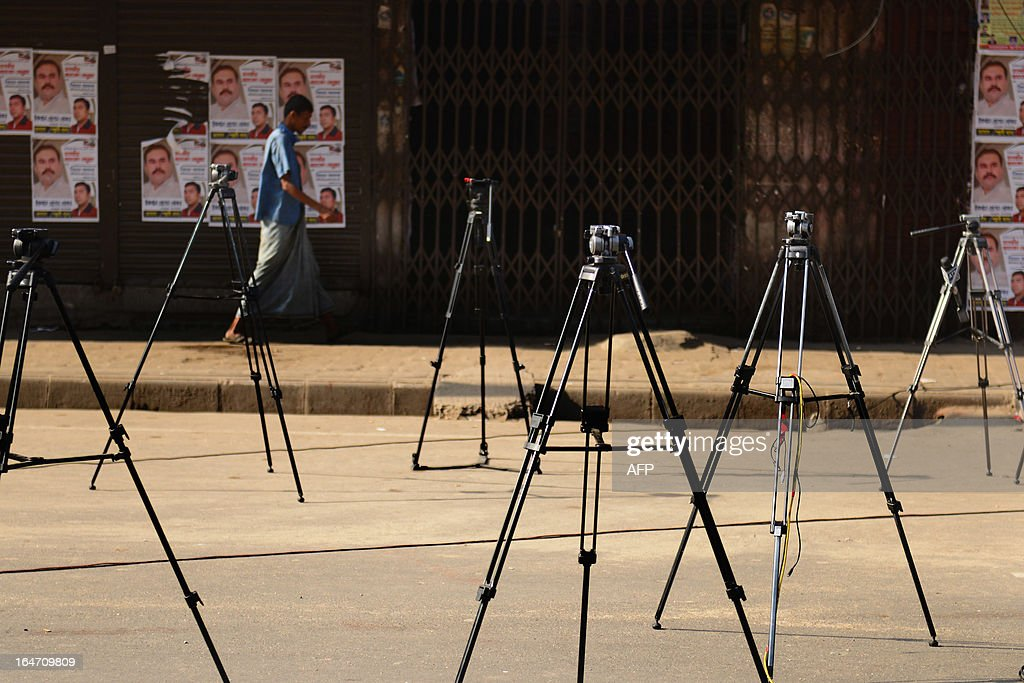 A Bangladeshi pedestrian passes the tripods of media personnel setup in front of Bangladesh Nationalist Party (BNP) party headquarters during a nationwide strike called by the opposition BNP in protest against the detention of their leaders, in Dhaka on March 27, 2013. The BNP and its allies enforced a 36 hours general strike across the country mainly to demand the release of more than 150 of their leaders and activists detained earlier this month. AFP PHOTO/Munir uz ZAMAN