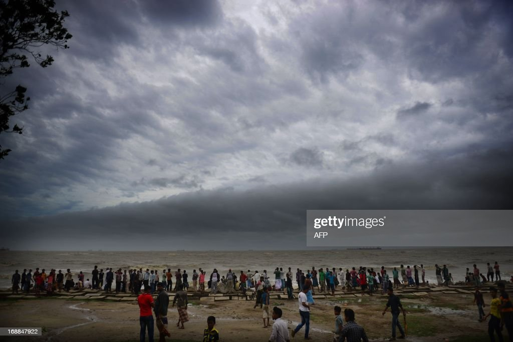 Bangladeshi pedestrians gather to watch the sea at a beach while Cyclone Mahasen heads towards landfall in Chittagong on May 16, 2013. A cyclone has slammed into the Bangladeshi coast as a million people hunkered down in evacuation shelters, including in a region of Myanmar torn by communal unrest. Four people died as Cyclone Mahasen hit Bangladesh's Patuakhali coast, officials said. Rain and strong winds lashed neighbouring Myanmar's northwest coast, home to tens of thousands of displaced Muslim Rohingya. AFP PHOTO/ Munir uz ZAMAN