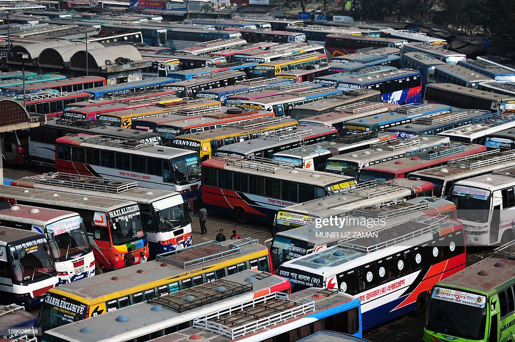 Bangladeshi pedestrians stand near parked buses at an inter-district bus terminal during a nationwide strike in Dhaka on January 6, 2013. Anti-government protesters set fire to cars and buses during the opposition alliance's day-long countrywide shutdown strike protesting the latest hike in fuel oil prices. AFP PHOTO/ Munir uz ZAMAN