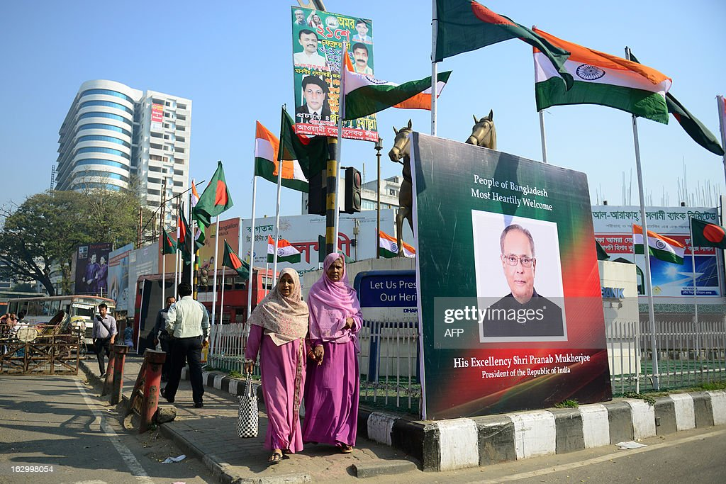 Bangladeshi pedestrians walk past a picture of Indian President Pranab Mukherjee on a street corner in Dhaka on March 3, 2013, at the start of a state visit. Mukherjee is on a three-day state visit to Bangladesh until March 5. AFP PHOTO/Munir uz ZAMAN