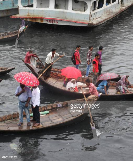 Bangladeshi people cross the River Buriganga during the rainy weather in Dhaka Bangladesh on 30 May 2017 All river transports have been suspended as...