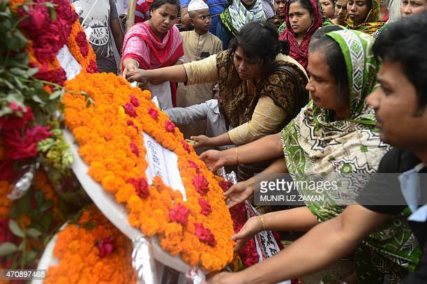 Bangladeshi people lay floral wreaths in memory of the victims of Rana Plaza building collapse as they mark the second anniversary of the disaster at...