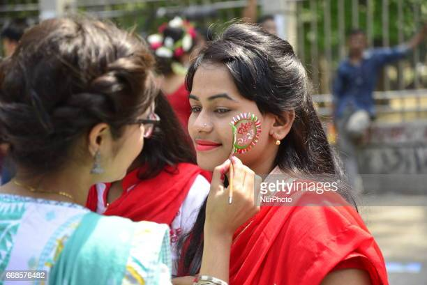 Bangladeshi people paints her face before participate in a parade to celebrate the first day of the Bangla New Year or quotPahela Baisshakhquot in...