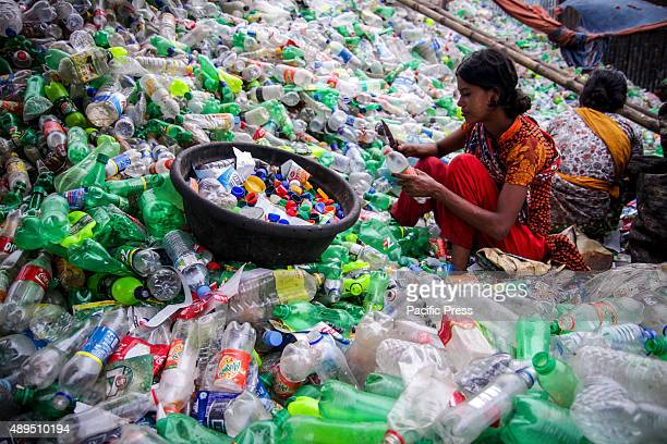 Bangladeshi people work in a plastic bottle recycling factory besides the river Buriganga in Dhaka