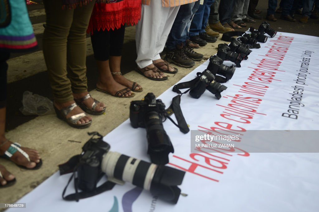 Bangladeshi photojournalists place their cameras over a banner as they form a human chain with social activists in Dhaka on August 30, 2013, as they protest the recent gang-rape of a female colleague in Mumbai, India. The gang-rape reignited anger about women's safety in India following a similar attack last year. AFP PHOTO/Munir uz ZAMAN