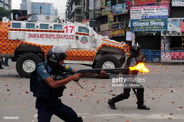 Bangladeshi police fire rubber bullets towards demonstrators during clashes with Islamists in Dhaka on May 5 2013 'At least one person was shot dead...