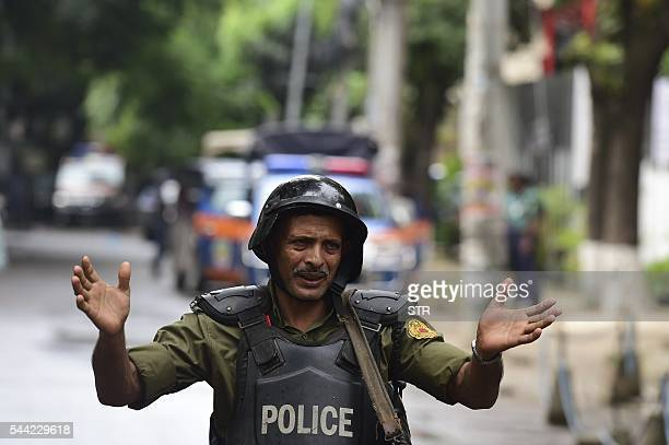 A Bangladeshi police officer gestures during a rescue operation as gunmen take position in a restaurant in the Dhakas highsecurity diplomatic...