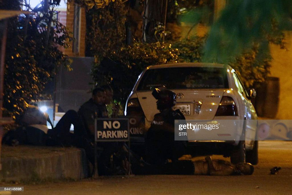 Bangladeshi police officers take cover as a man lies on the ground near the Holey Artisan Bakery restaurant during an attack by unidentified gunmen in Dhaka's high-security diplomatic district on July 2, 2016. Gunmen stormed a crowded restaurant popular with foreigners in the Bangladeshi capital on July 1 night, apparently taking diners hostage and sparking a firefight with police in which at least two officers were killed, police and witnesses said. / AFP / STR
