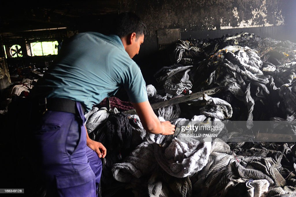 A Bangladeshi police official sifts through burnt clothes inside a gutted garment factory in Dhaka on May 9, 2013. A fire at a garment factory killed at least eight people May 9 in the latest disaster to hit Bangladesh's textile industry, still reeling from the deaths of more than 900 people in a building collapse. AFP PHOTO/Munir uz ZAMAN