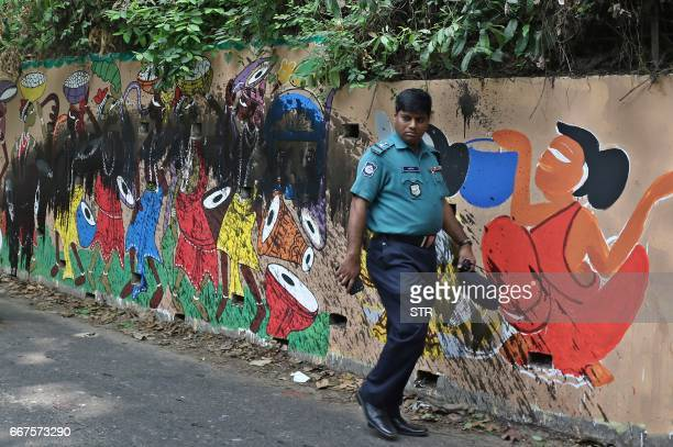 A Bangladeshi police official walks past vandalised graffiti celebrating the New Year in Chittagong on April 12 2017 Unknown miscreants April 12...