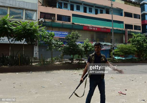 Bangladeshi police stand guard in front of the hotel building that was stormed by Bangladesh security personnel during an operation on a militant...
