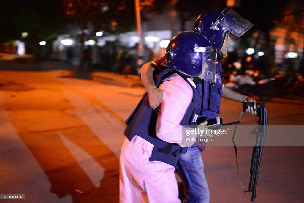 Bangladeshi police take cover near a restaurant that has been attacked by unidentified gunmen on July 1 2016 in Dhaka Bangladesh Gunmen have taken at...