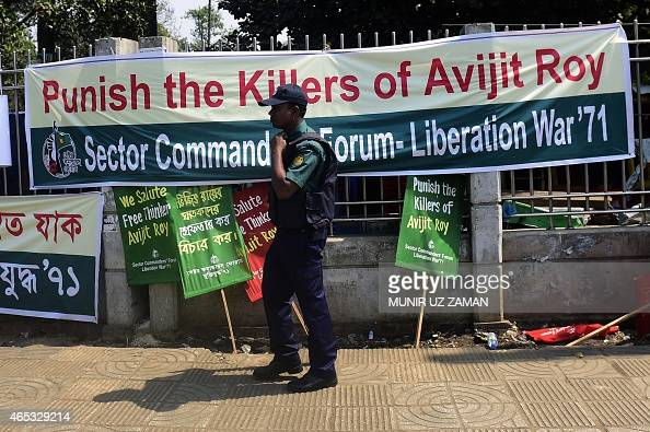 A Bangladeshi policeman walks past a banner for slain US blogger of Bangladeshi origin and founder of the MuktoMona blog site Avijit Roy during an...