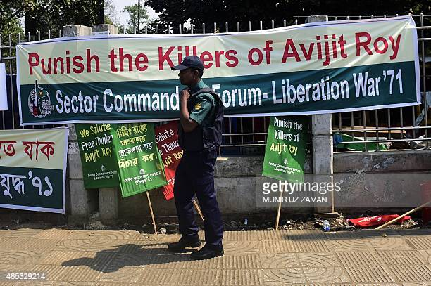 A Bangladeshi policeman walks past a banner for slain US blogger of Bangladeshi origin and founder of the MuktoMona blog site Avijit Roy during an...