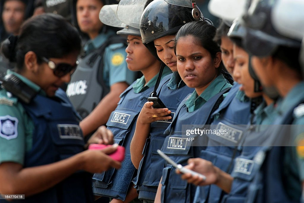 Bangladeshi policewomen use their cellular telephones as they stand guard during a nationwide strike called by the opposition Bangladesh Nationalist Party (BNP) in protest against the detention of their leaders, in Dhaka on March 28, 2013. Schools and businesses were shut across Bangladesh on the second day of a general strike called by the country's main opposition party and Islamic allies. AFP PHOTO/Munir uz ZAMAN