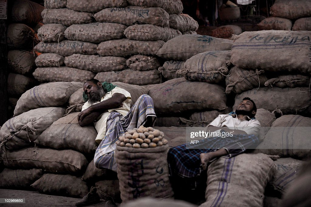 Bangladeshi potato vendors sleep at Karwan Bazar in Dhaka on October 7, 2009. Karwan Bazar is one of the largest wholesale marketplaces in the Bangladeshi capital. According to statistics from 2002, the market had 1255 stores generating a daily revenue of 50 million Bangladeshi Taka (USD 729,000). AFP PHOTO/Munir uz ZAMAN