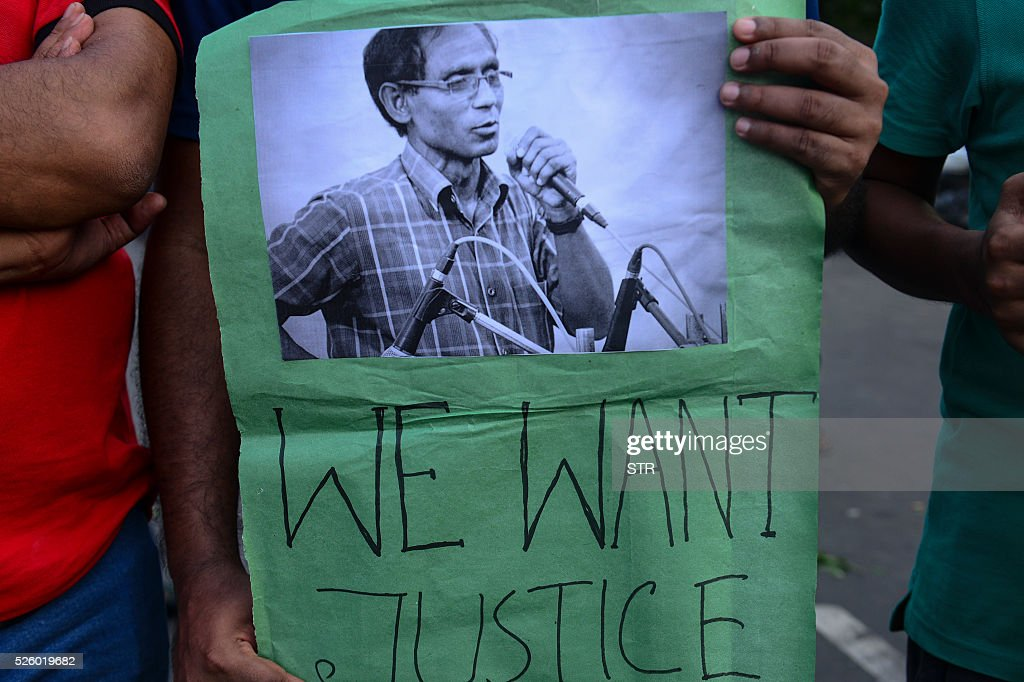 A Bangladeshi protester holds a placard as others form a human chain during a demonstration against the killing of a university professor in Dhaka on April 29, 2016. Bangladesh police arrested an Islamist student on April 24 over the hacking to death of a professor one day earlier, the latest such killing claimed by the Islamic State group. / AFP / STR