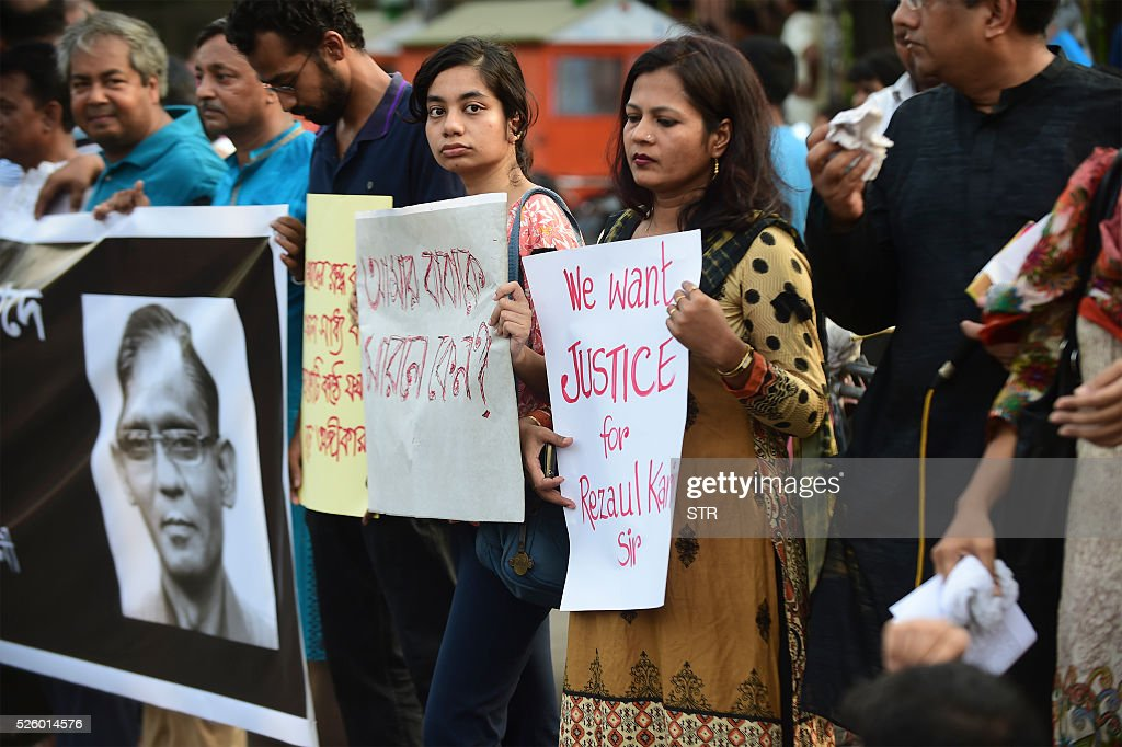 Bangladeshi protesters and former Rajshahi University students hold placards and form a human chain during a demonstration against the killing of a university professor in Dhaka on April 29, 2016. Bangladesh police arrested an Islamist student on April 24 over the hacking to death of a professor one day earlier, the latest such killing claimed by the Islamic State group. / AFP / STR