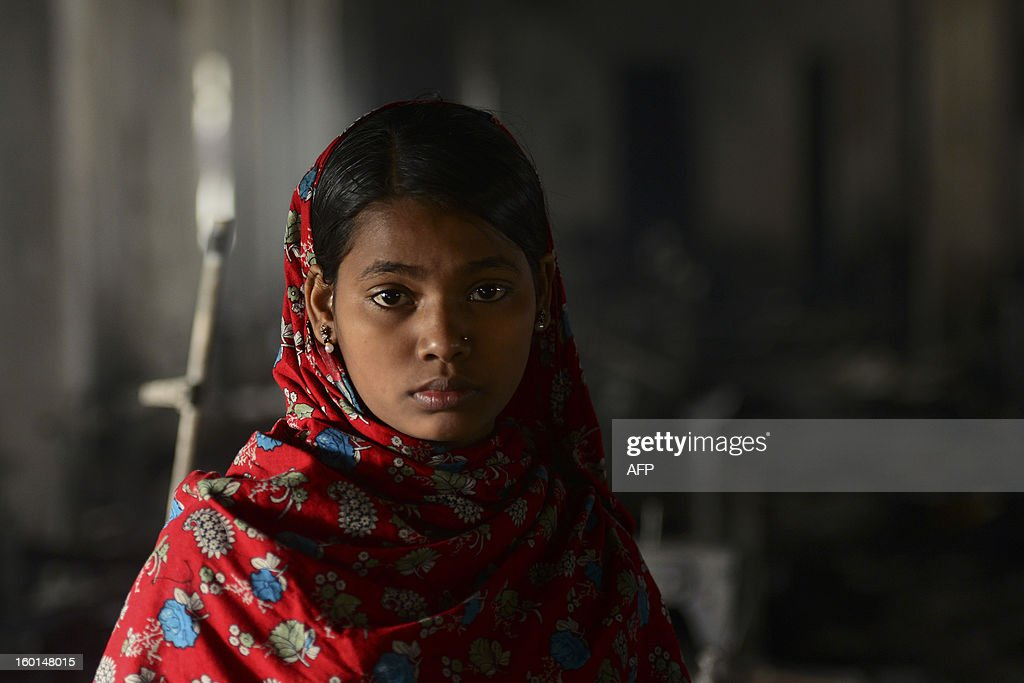 Bangladeshi Razia, 20 who worked in this garment factory, looks on in front of the devastation after a fire swept though the premises, in Dhaka on January 27, 2013. At least seven female workers were killed on January 26 after a blaze swept through a small garment factory in the Bangladeshi capital of Dhaka, police and fire officials said. AFP PHOTO / Munir uz ZAMAN