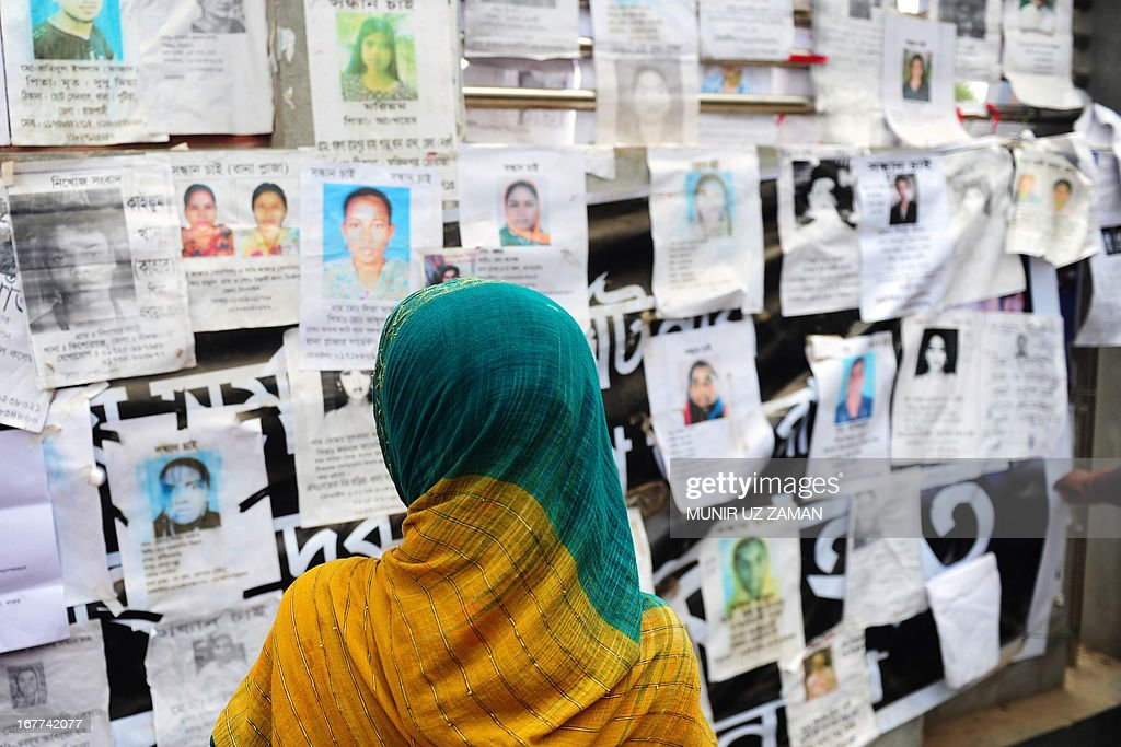 A Bangladeshi relative looks at a board posting notices of missing and dead workers of an eight-storey building collapse in Savar, on the outskirts of Dhaka, on April 29, 2013. Thousands of Bangladeshi garment workers walked out of their factories Monday, demanding the death penalty for the owner of a tower block that collapsed and killed at least 381 of their colleagues. AFP PHOTO/MUNIR UZ ZAMAN