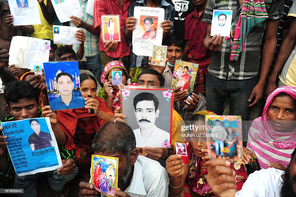 Bangladeshi relatives hold photos of the missing and dead workers three days after an eight-storey building collapsed in Savar, on the outskirts of Dhaka on April 27, 2013. Police arrested two textile bosses over a Bangladeshi factory disaster as the death toll climbed to 332 and distraught relatives lashed out at rescuers trying to detect signs of life. AFP PHOTO/ Munir uz ZAMAN