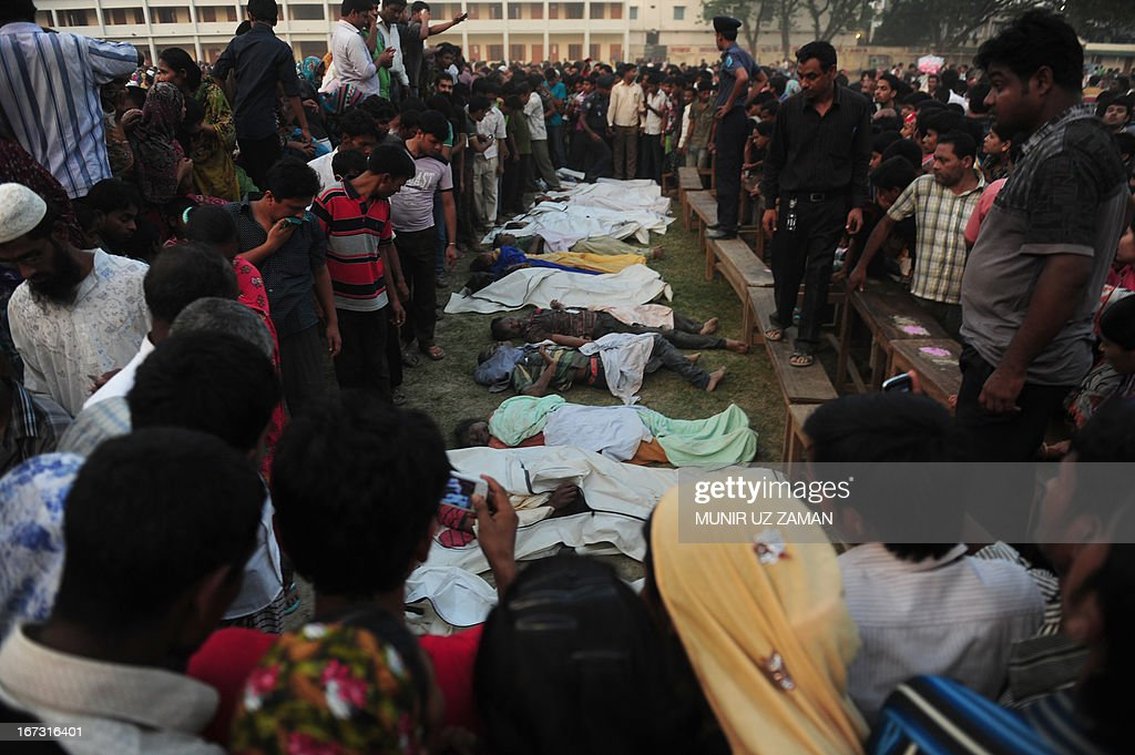 Bangladeshi relatives look at dead bodies after a building collapse in Savar, on the outskirts of Dhaka, on April 24, 2013. An eight-storey building containing several garment factories collapsed in Bangladesh, killing at least 82 people and further highlighting safety problems in the clothing industry. Armed with concrete cutters and cranes, hundreds of fire service and army rescue workers struggled to find survivors in the mountain of concrete and mangled steel, which resembled the aftermath of an earthquake. AFP PHOTO/ Munir uz ZAMAN