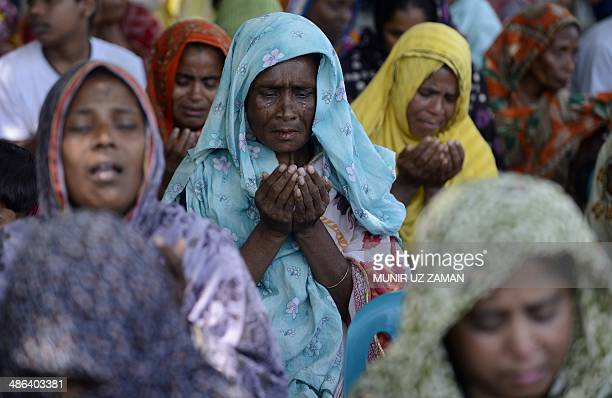 Bangladeshi relatives of victims of the Rana Plaza building collapse pray during an event marking the first anniversary of the disaster in Dhaka on...