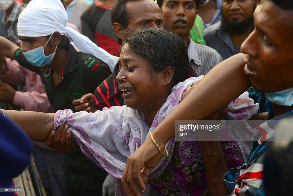 Bangladeshi relatives react after looking at the coffin of a victim following the collapse of an eight-storey building in Savar, on the outskirts of Dhaka on April 28, 2013. A fire broke out in the wreckage of a Bangladesh factory complex at night on April 28, killing the last known survivor from the building's collapse five days earlier, the national fire chief said. AFP PHOTO/Mnuir uz ZAMAN