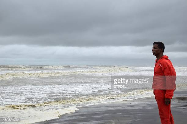 A Bangladeshi rescue official looks out towards the ocean from a beach in Cox's Bazar on July 30 as Cyclone Komen approaches A cyclone set to hit the...