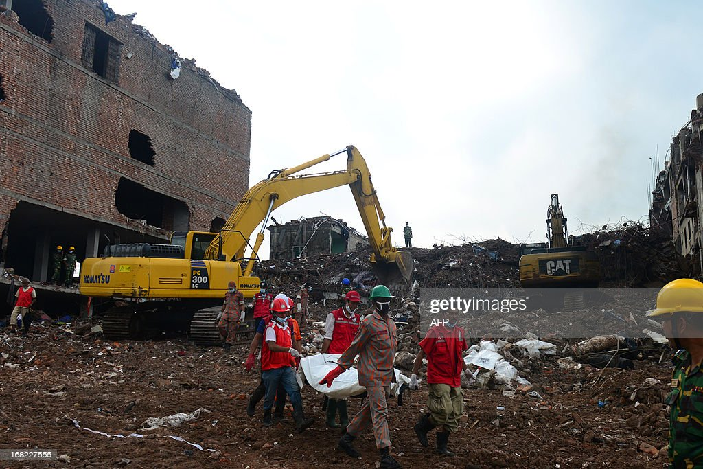 Bangladeshi rescue personnel carry stretchers with the remains of garment workers from the site of a collapsed building as heavy machinery clear the debris in Savar on the outskirts of Dhaka, on May 7, 2013. Hundreds of survivors of Bangladesh's worst industrial disaster have received wages on Tuesday as the death toll from the collapse of a nine-storey building passed 700, officials said. AFP PHOTO/ Munir uz ZAMAN