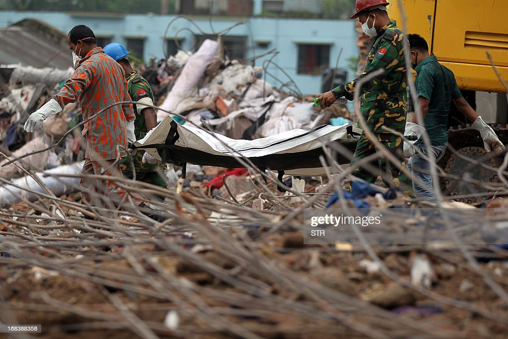 Bangladeshi rescue personnel carry stretchers with the remains of garment workers from the site of a collapsed building in Savar on the outskirts of Dhaka, on May 9, 2013. The death toll from Bangladesh's worst industrial disaster exceeded 900 on Thursday as rescuers pulled out dozens more bodies from the rubble of a nine-storey building that collapsed outside Dhaka last month.