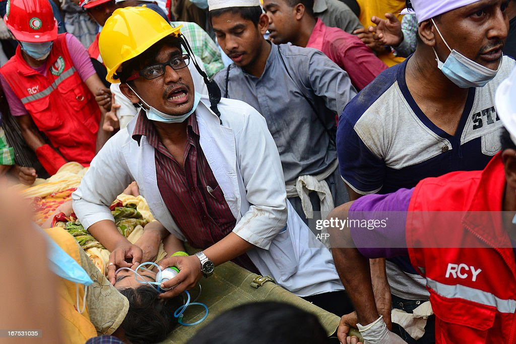 Bangladeshi rescue worker assists a survivor after she was recovered, 60 hours later, from the rubble of a collapsed eight-storey building in Savar, on the outskirts of Dhaka, on April 26, 2013. A total of 304 people are so far known to have died after the eight-storey building collapsed in the town of Savar on Wednesday morning. Rescuers are racing against time to find more survivors in searing temperatures, watched on by hundreds of anxious relatives waiting for news of their missing loved ones. AFP PHOTO/ MUNIR UZ ZAMAN
