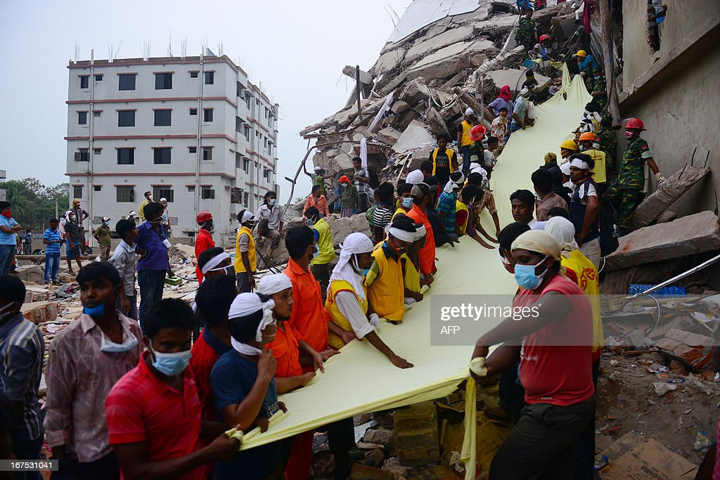 Bangladeshi rescue worker holds a length of textile as a slide to move dead victims recovered 60 hours later, from the rubble of a collapsed eight-storey building in Savar, on the outskirts of Dhaka, on April 26, 2013. A total of 304 people are so far known to have died after the eight-storey building collapsed in the town of Savar on Wednesday morning. Rescuers are racing against time to find more survivors in searing temperatures, watched on by hundreds of anxious relatives waiting for news of their missing loved ones.