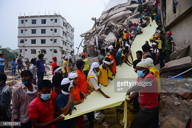 Bangladeshi rescue worker holds a length of textile as a slide to move dead victims recovered 60 hours later from the rubble of a collapsed...