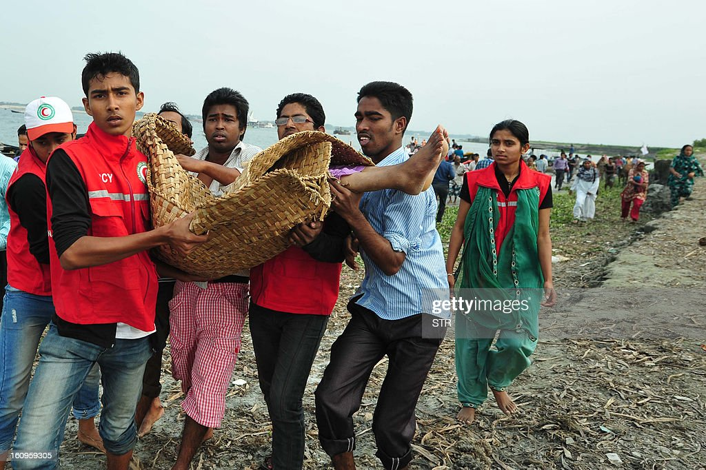 Bangladeshi rescue workers carry the dead body of a drowned passenger after a ferry accident in Munshiganj on February 8, 2013. Scores of people were missing after a ferry carrying around 100 passengers sank following a collision on a river in Bangladesh Friday, the latest in a series of disasters blamed on lax safety standards. AFP PHOTO