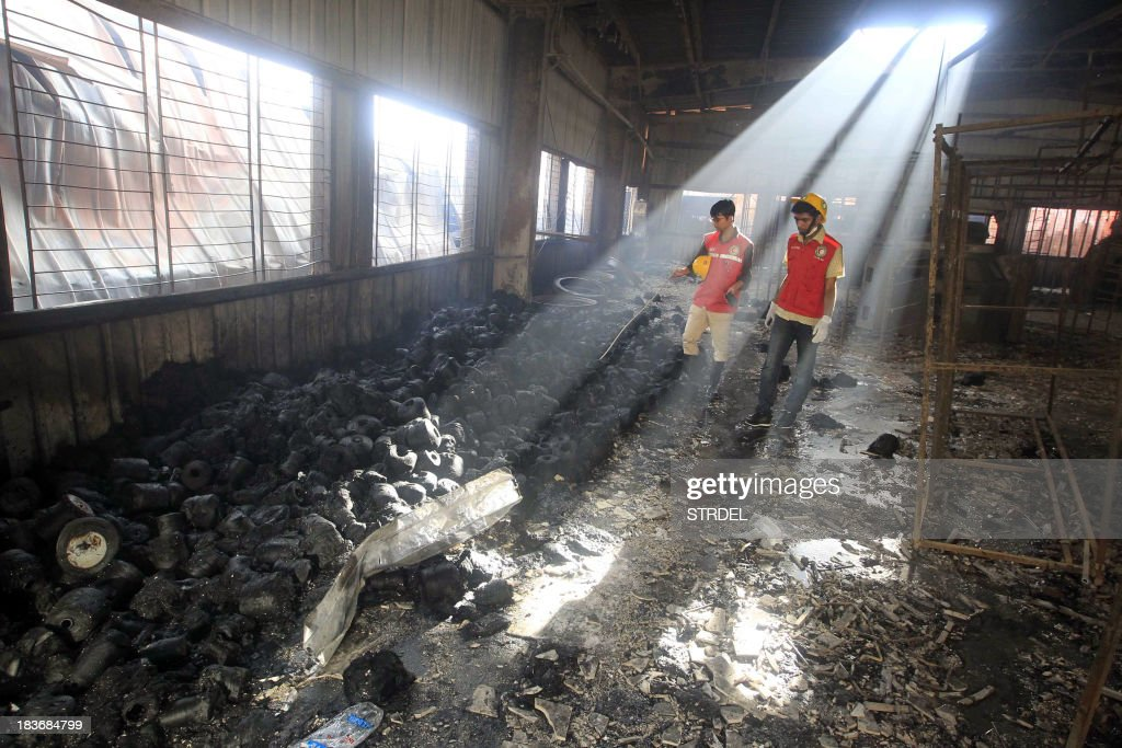 Bangladeshi rescue workers look on at the scene following a blaze that engulfed a garment factory in Sripur on October 9, 2013. A huge fire at a Bangladeshi factory where workers were making clothes for labels such as Gap and H&M has killed seven people in the latest disaster to blight the country's garment industry. AFP PHOTO/ STR