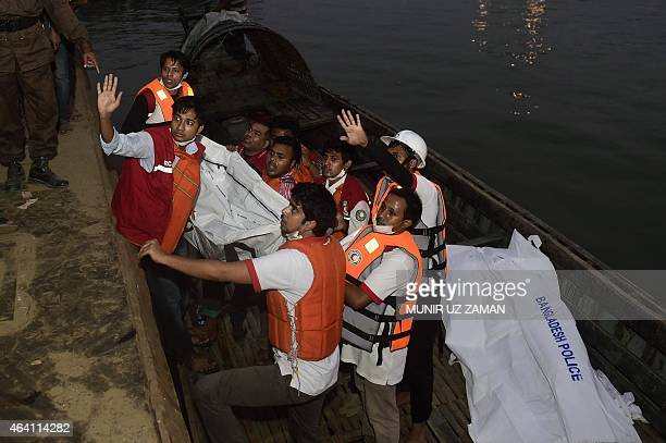 Bangladeshi rescue workers recover the body of a victim after a ferry accident at Paturia some 70kms east of Dhaka on February 22 2015 Sixteen people...