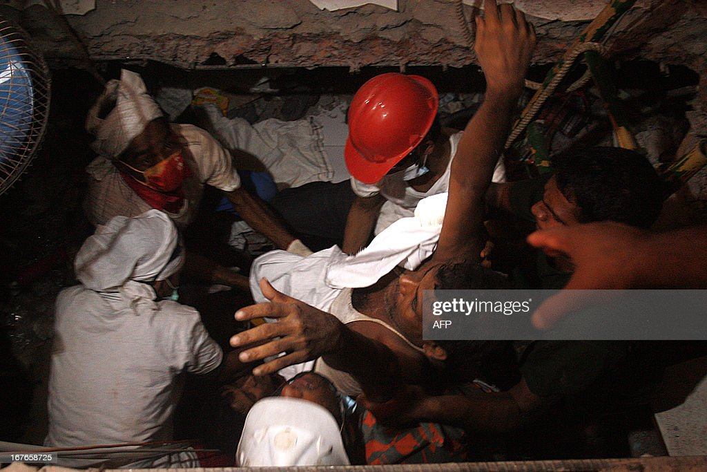 Bangladeshi rescuers carry a survivor who was recovered, on April 27, 2013 in Savar, three days after an eight-storey building collapsed. Bangladesh made a string of arrests today over the collapse of a factory complex which killed at least 351 people as exhausted rescuers battled to find more survivors among the corpses. AFP PHOTO/STR