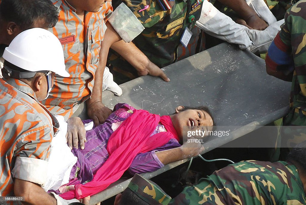 Bangladeshi rescuers retrieve garment worker Reshma from the rubble of a collapsed building in Savar on May 10, 2013, seventeen days after the eight-storey building collapsed. The death toll from last month's collapse of a garment factory complex in Bangladesh rose past 1,000 as piles of bodies were found in the ruins of a stairwell where victims had sought shelter. AFP PHOTO/STR
