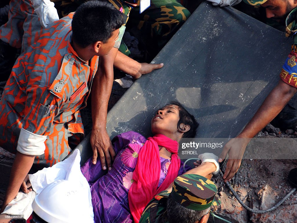 Bangladeshi rescuers retrieve garment worker Reshma from the rubble of a collapsed building in Savar on May 10, 2013, seventeen days after an eight-storey building collapsed. The death toll from last month's collapse of a garment factory complex in Bangladesh rose past 1,000 as piles of bodies were found in the ruins of a stairwell where victims had sought shelter. AFP PHOTO/STR