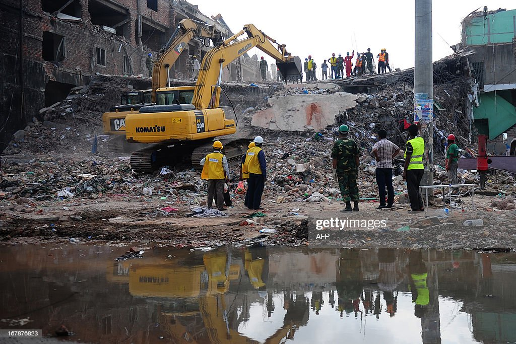 Bangladeshi rescuers use a digger to move debris as Bangladeshi Army personel continue the second phase of a rescue operation using heavy equipment after an eight-storey building collapsed in Savar, on the outskirts of Dhaka, on May 2, 2013. Bangladesh authorities have suspended the mayor of Savar satellite town outside the capital for approving the faulty construction of a building that collapsed last week, killing 429 people. AFP PHOTO/ Munir uz ZAMAN