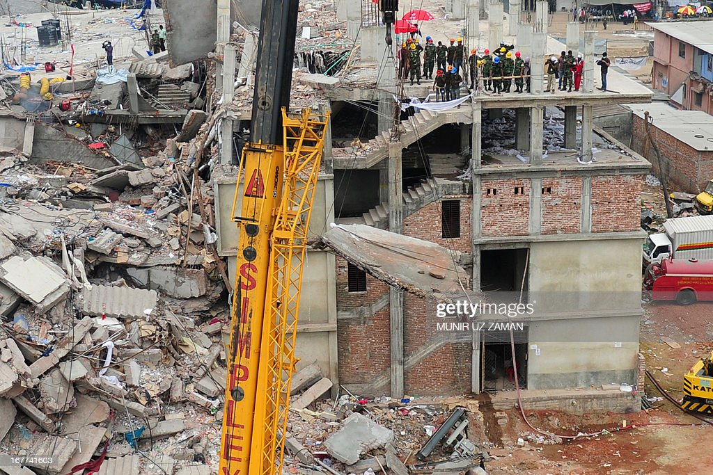 Bangladeshi rescuers work as Bangladeshi Army personel begin the second phase of the rescue operation using heavy equipment after an eight-storey building collapsed in Savar, on the outskirts of Dhaka, on April 29, 2013. Thousands of Bangladeshi garment workers walked out of their factories Monday, demanding the death penalty for the owner of a tower block that collapsed and killed at least 381 of their colleagues. AFP PHOTO/MUNIR UZ ZAMAN