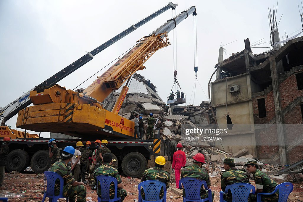Bangladeshi rescuers work as Bangladeshi Army personel begin the second phase of the rescue operation using heavy equipment after an eight-storey building collapsed in Savar, on the outskirts of Dhaka, on April 29, 2013. Thousands of Bangladeshi garment workers walked out of their factories Monday, demanding the death penalty for the owner of a tower block that collapsed and killed at least 381 of their colleagues.
