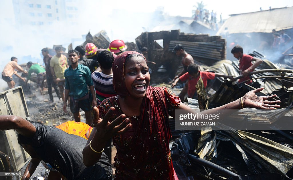 A Bangladeshi resident cries in front of the ashes of a slum which was engulfed by a fire in Dhaka on February 27, 2013. At least 300 shanties were gutted in the Kallyanpur's Natun Bazar slum fire in Dhaka, but no casualties took place, police said. AFP PHOTO/Munir uz ZANAN