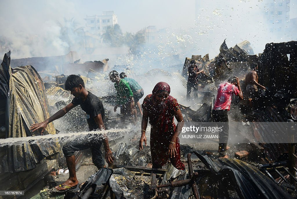 Bangladeshi residents search for household belongings in a slum that was engulfed by a fire in Dhaka on February 27, 2013. At least 300 shanties were gutted in the Kallyanpur's Natun Bazar slum fire in Dhaka, but no casualties took place, police said. AFP PHOTO/ Munir uz ZANAN