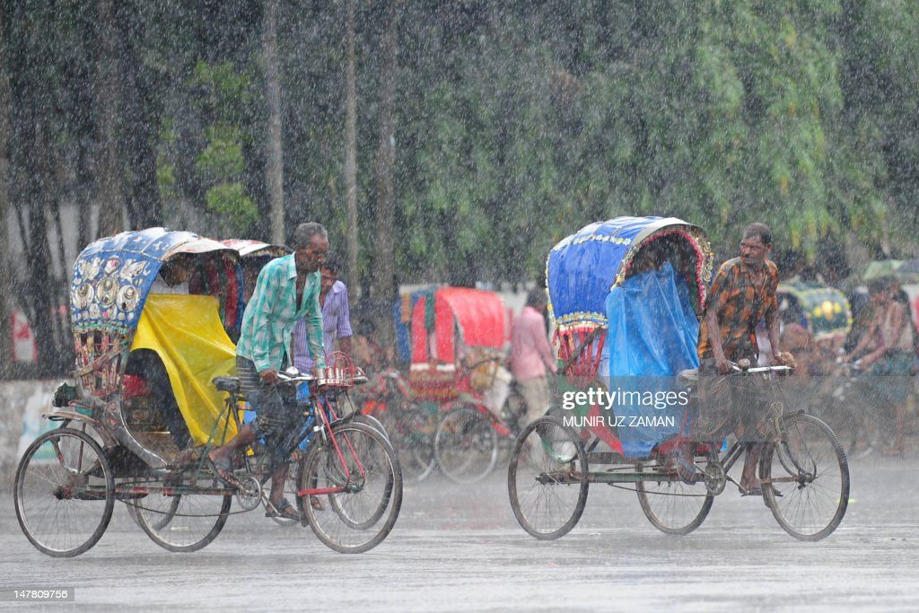 Bangladeshi rickshaw drivers pedal their vehicles through a heavy downpour in Dhaka on July 3, 2012. At least 100 people have been killed last week in Bangladesh's Chittagong, Cox's Bazar, Bandarban and Sylhet districts due to landslides, house collapses, lightning, electrocution and drowning following heavy torrential rains. AFP PHOTO/Munir uz ZAMAN